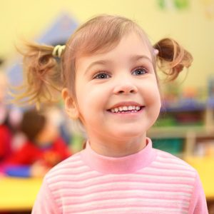 A smiling young girl at school with colorful objects in the background.